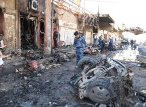 Iraqi security forces inspect the site of a bomb attack in Hilla, Iraq